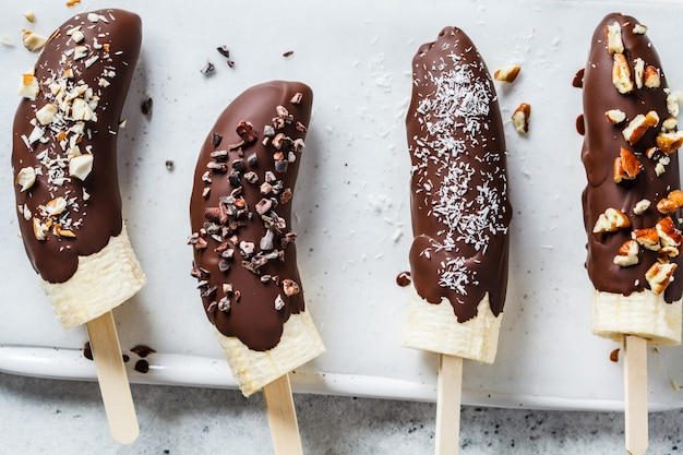 Veganes dessert für kinder. banane in dunkler schokolade mit nüssen.