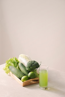 Veganes diätessen. detox-getränke. frisch gepresste säfte und smoothies aus gemüse, holztablett, zutaten. platz kopieren