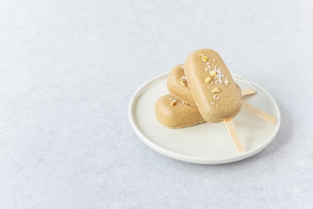 Veganes eis am stiel mit schoko-cashewnüssen und mangostücken auf einem teller