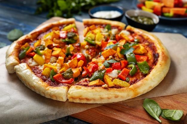 Veganes essen. gesunde pizza mit gemüse auf blauem hintergrund
