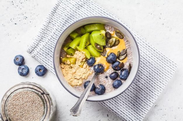 Veganes frühstück. chia-pudding mit kiwi, blaubeeren und erdnussbutter, draufsicht.