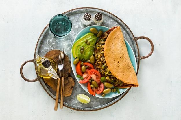 Veganes frühstück mit glutenfreiem eifreiem kichererbsenomelett mit gebratenen pilzen und lauch.