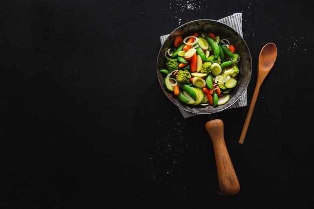 Veganes gemüse in der pfanne gebraten oder bereit zum kochen auf dem tisch