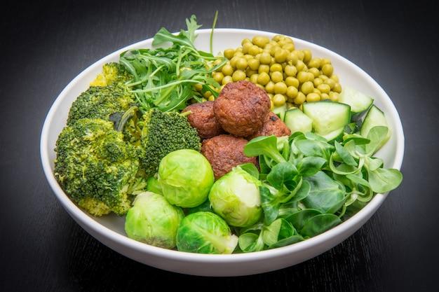 Veganes gericht mit soja frikadellen und grünem gemüse