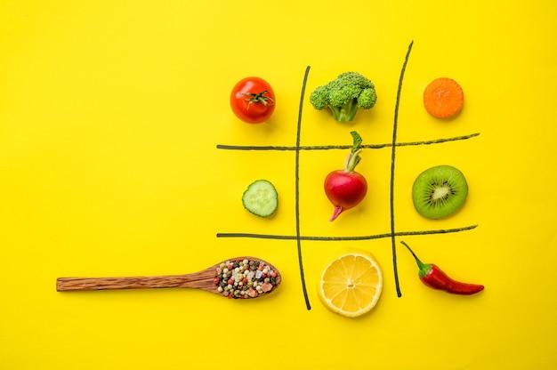 Veganes kreuz-null-spiel lokalisiert auf gelbem hintergrund. bio-vegetarisches essen, lebensmittelsortiment, natürliche öko-produkte, konzept für einen gesunden lebensstil