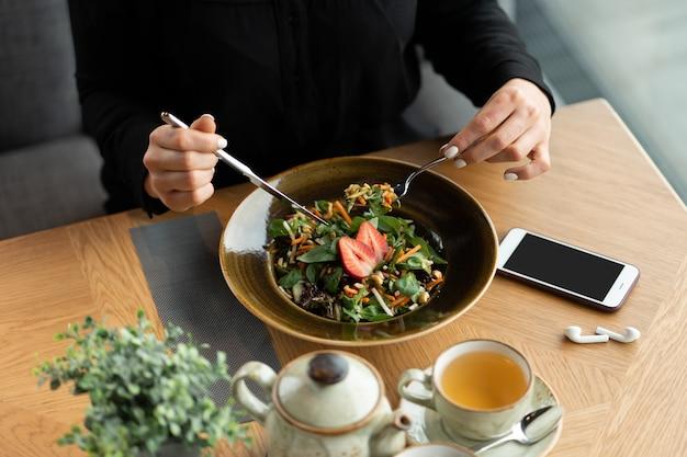 Veganes mädchen speist in einem café. ein gesundes mittagessen mit gemüsesalat und frischen erdbeeren. flache schärfentiefe, unscharfer hintergrund.