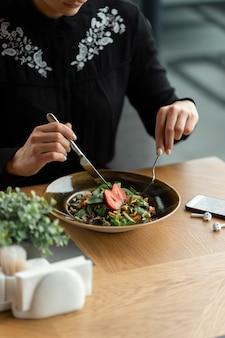 Veganes mädchen speist in einem restaurant. gemüsegemüsesalat, garniert mit frischen erdbeeren. flache schärfentiefe, unscharfer hintergrund