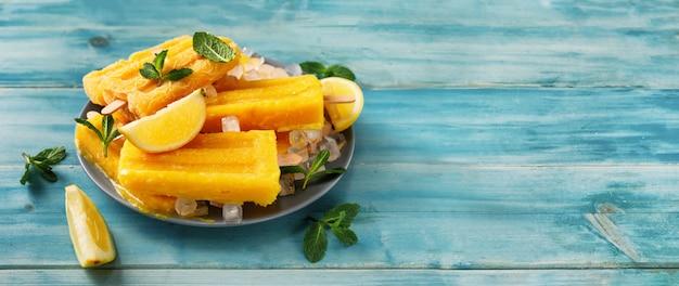 Veganes mango-sorbet-eis am stiel auf trendigem türkisfarbenem hintergrund