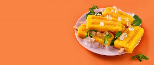 Veganes mangosorbet-eis am stiel auf trendigem lebendigem orangefarbenem hintergrund