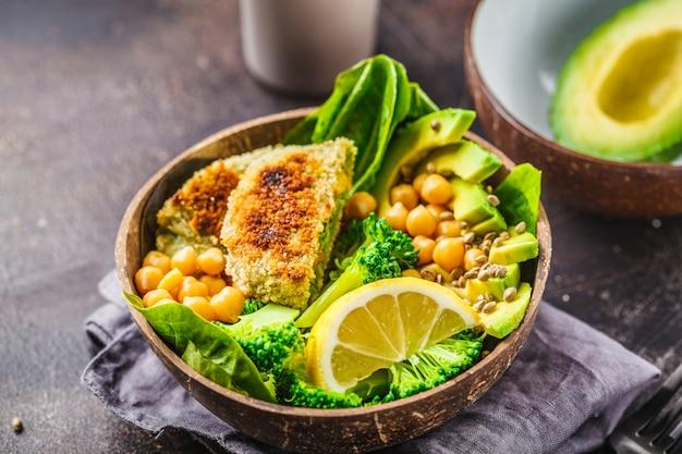 Veganes mittagessen in einer kokosnussschale: grüne burger mit salat und kichererbsen.