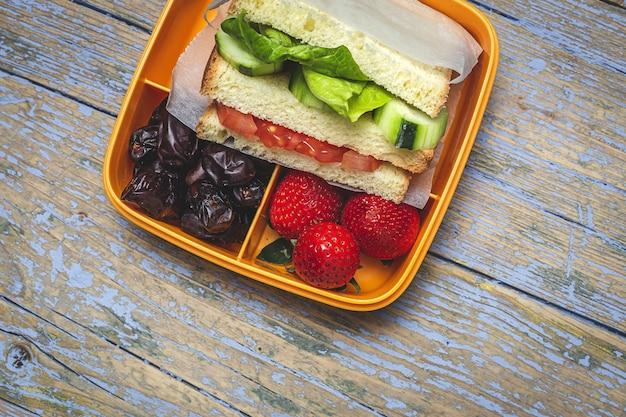 Veganes sandwich im plastikbehälter auf hölzernem hintergrund