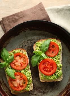 Veganes sandwich mit avocado und gemüse auf pfanne, auf holztisch