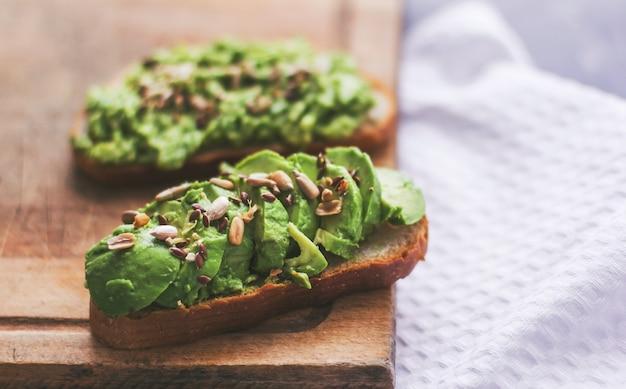 Veganes sandwich mit avocado und samen auf einem holzbrett