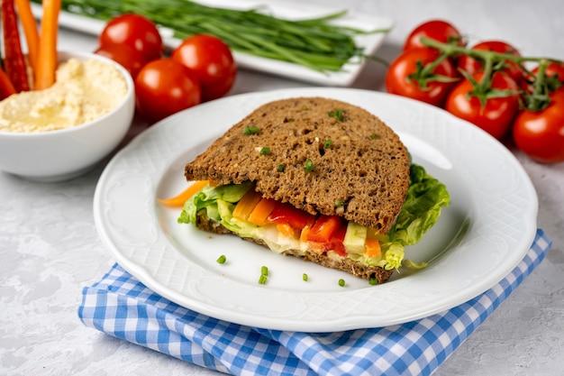 Veganes sandwich mit hummus und gemüse auf weißem teller