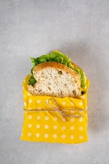 Veganes sandwich mit sauerteigbrot in wiederverwendbarem bienenwachstuch
