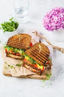 Veganes sandwich mit tofu, hummus, avocado, tomate und sprossen.
