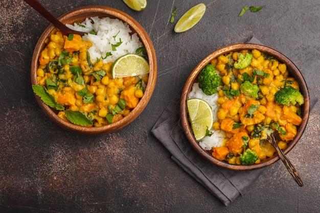 Veganes süßkartoffel-kichererbsen-curry in der holzschale auf einem dunklen tisch, draufsicht. gesundes vegetarisches lebensmittelkonzept.