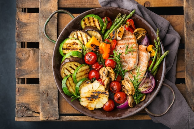Veganes, vegetarisches, saisonales, sommerliches essenskonzept. gegrilltes gemüse in einer pfanne auf einem dunklen schwarzen tisch. draufsicht flach legen hintergrund