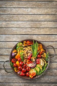 Veganes, vegetarisches, saisonales, sommerliches essenskonzept. gegrilltes gemüse in einer pfanne auf einem holztisch. draufsicht flach kopieren raumhintergrund
