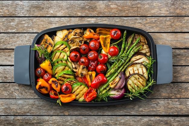 Veganes, vegetarisches, saisonales, sommerliches essenskonzept. gegrilltes gemüse in einer pfanne auf einem holztisch. draufsicht flach legen hintergrund