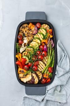Veganes, vegetarisches, saisonales, sommerliches essenskonzept. gegrilltes gemüse in einer pfanne auf einem tisch. draufsicht flach legen hintergrund