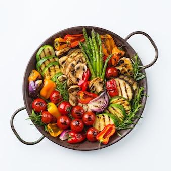 Veganes, vegetarisches, saisonales, sommerliches essenskonzept. gegrilltes gemüse in einer pfanne auf einem weißen tisch, isoliert. draufsicht flach legen hintergrund