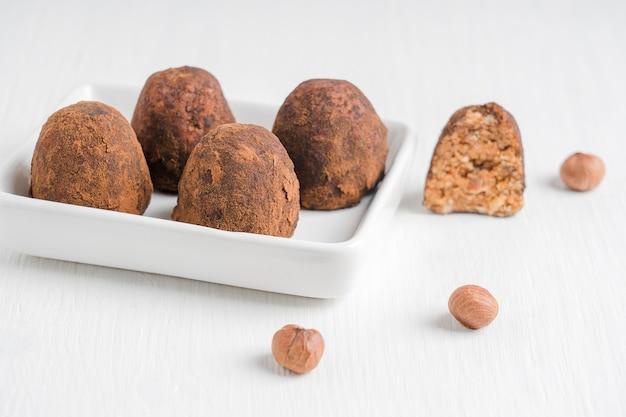 Vegetarische bio-schokoladentrüffel aus haselnüssen mit kakaopulver auf teller auf einem tisch serviert