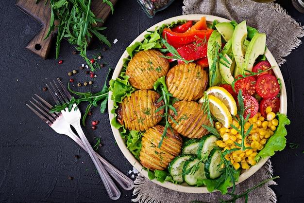 Vegetarische buddha-schüssel. rohes gemüse und ofenkartoffeln in der schüssel. veganes essen.