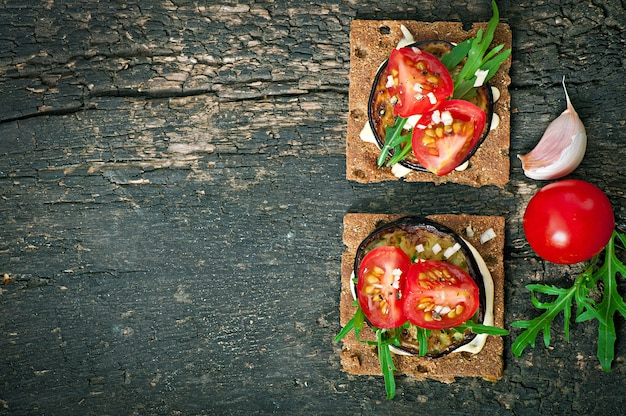 Vegetarische diät-knäckebrot-sandwiches mit knoblauch-frischkäse, gerösteten auberginen, rucola und kirschtomaten auf altem holz