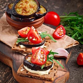 Vegetarische diät-knäckebrotsandwiche mit knoblauchcremekäse, gebratenen auberginen-, arugula- und kirschtomaten auf alter holzoberfläche