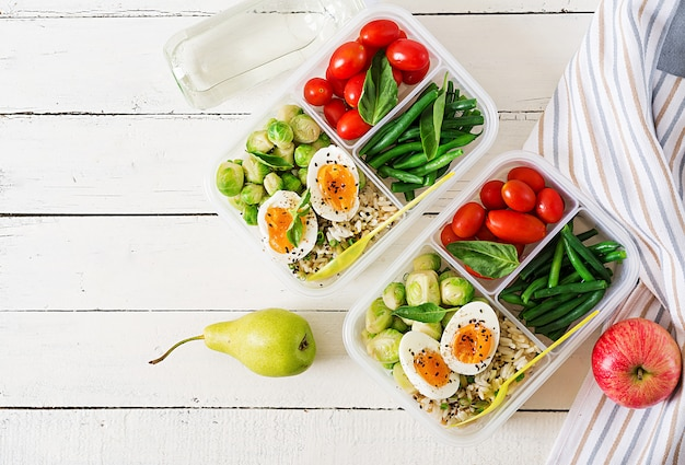 Vegetarische essenszubereitungsbehälter mit eiern, rosenkohl, grünen bohnen und tomaten. abendessen in der brotdose. draufsicht. flach liegen
