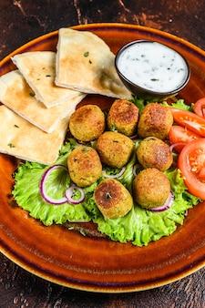 Vegetarische falafel mit fladenbrot, frischem gemüse und sauce auf einem teller. dunkler hintergrund. ansicht von oben.