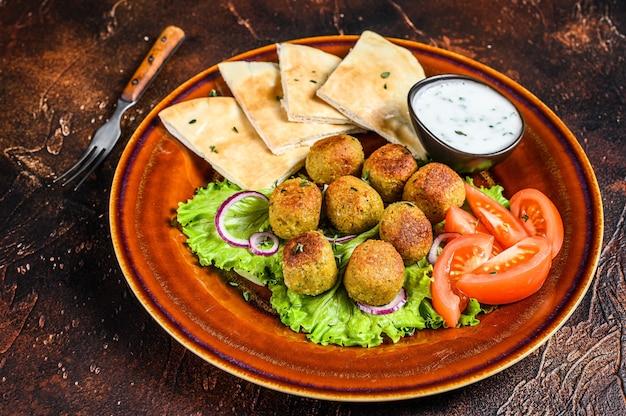 Vegetarische falafel mit fladenbrot, frischem gemüse und sauce auf einem teller