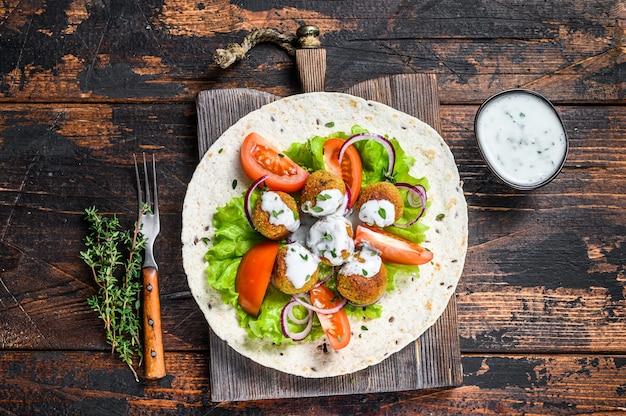 Vegetarische falafel mit gemüse und tzatziki-sauce auf einem tortillabrot