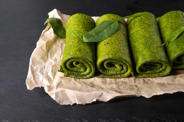 Vegetarische grüne pfannkuchen. spinatpfannkuchen auf einem backpapier aufgerollt. spinat vegetarische rezepte.