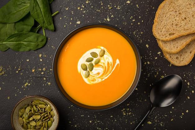 Vegetarische hausgemachte kürbis-karotten-suppe mit sahne und brot flach lag auf dunklem hintergrund