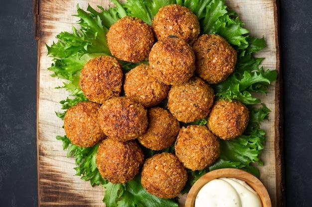 Vegetarische kichererbsen-falafelbällchen auf rustikalem holzbrett.