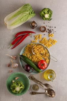 Vegetarische kochnudeln mit gemüse, rohen zutaten auf leichtem beton