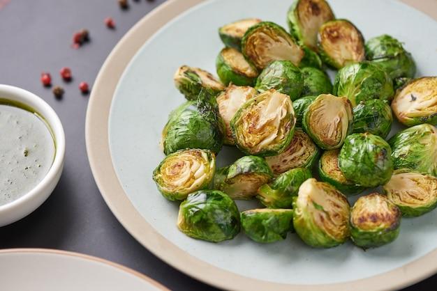 Vegetarische küche. hausgemachte rosenkohl mit olivenöl in der platte auf dem tisch geröstet. copyspace, draufsicht, flatlay.