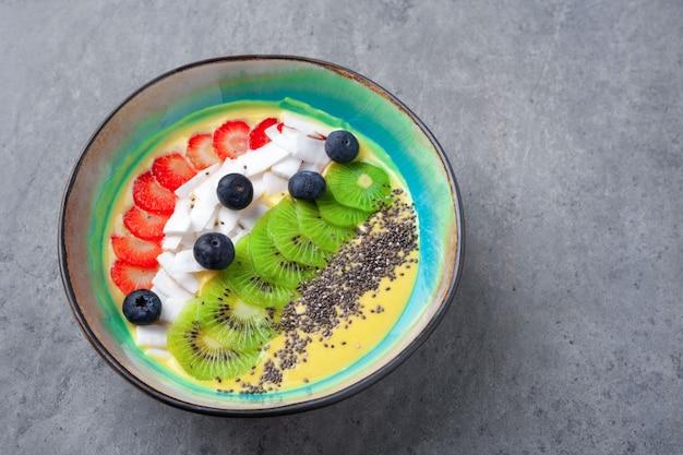 Vegetarische mango-smoothie-schüssel mit kiwi, chia, kokosnuss, blaubeere, erdbeere