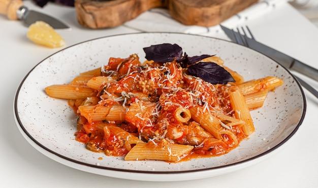 Vegetarische nudeln mit auberginen-tomatensauce und lila basilikum. italienische küche