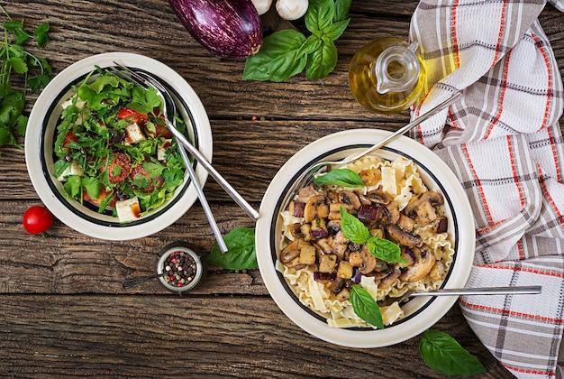 Vegetarische nudeln mit champignons und auberginen, auberginen und salat.