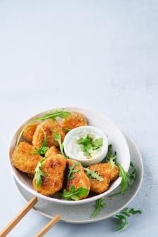 Vegetarische nuggets mit veganer dip-sauce und rucola-blättern auf einem licht