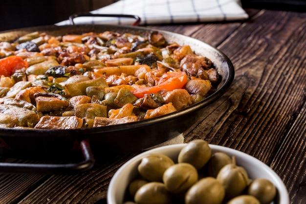 Vegetarische paella und oliven serviert auf einem holztisch tisch serviert für ein familienessen mit mediterranem essen.