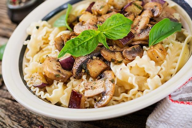 Vegetarische pasta mit champignons und auberginen, auberginen. italienisches essen. veganes essen.