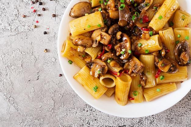 Vegetarische pasta rigatoni mit pilzen und chilischoten in weißer schüssel auf grauem tisch. veganes essen. flach liegen. draufsicht