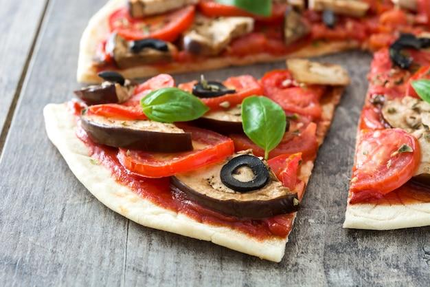 Vegetarische pizza mit aubergine, tomate, schwarzen oliven, oregano und basilikum auf holztisch