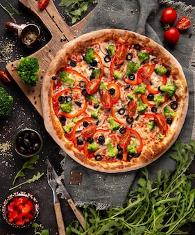 Vegetarische pizza mit brokkoli, rotem pfeffer, tomate und schwarzen oliven auf dem holzschrank