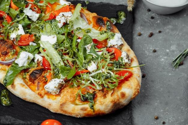 Vegetarische pizza mit käsetomaten und gemüse.
