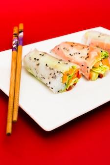 Vegetarische reispapierrollen angefüllt mit gemüse auf platte mit hölzernen essstäbchen